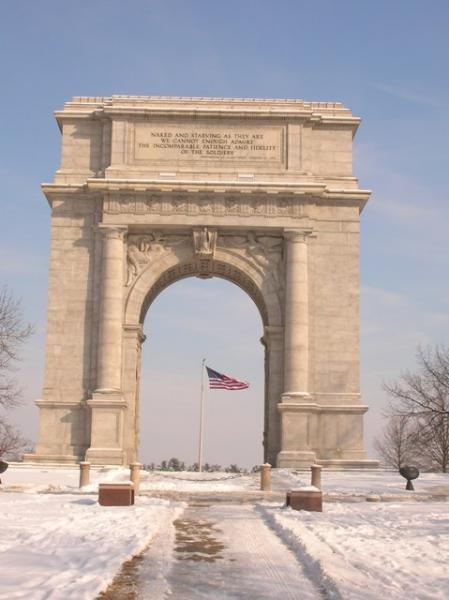Valley Forge Arch with American flag flying on a snowy day
